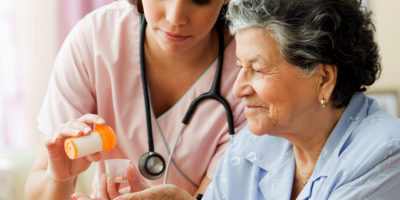 B16CP0 Hispanic nurse helping senior woman with medication--royalty free--nurse--paitent--at home health care--pills